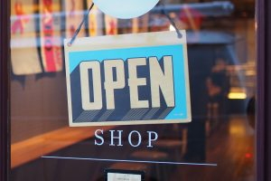Blue open sign on shop door with words open written underneath